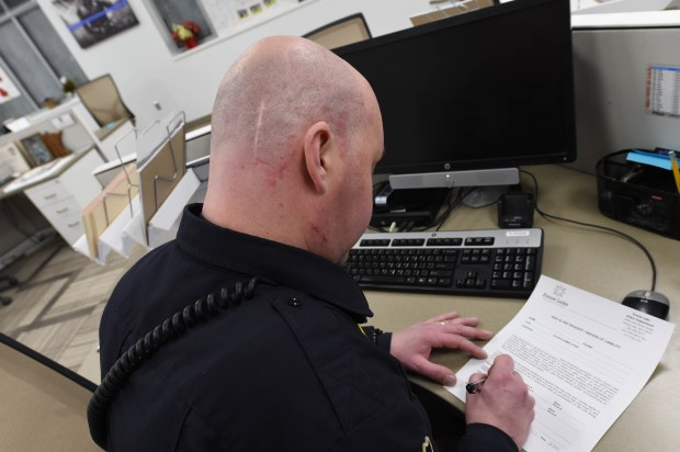 Forest Lake Patrol Officer Troy Meyer, who has a large scar on the back of his head from brain surgery he underwent in 2014, does some deskwork in the office, Wednesday, March 8, 2017. Scott Takushi / Pioneer Press