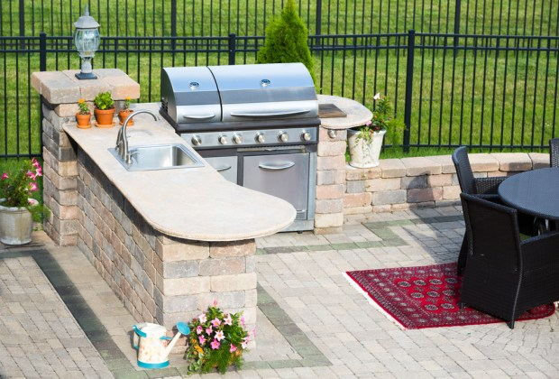 Easy-to-clean countertops, stainless steel grills and plenty of storage space are key factors to consider for an outdoor kitchen.