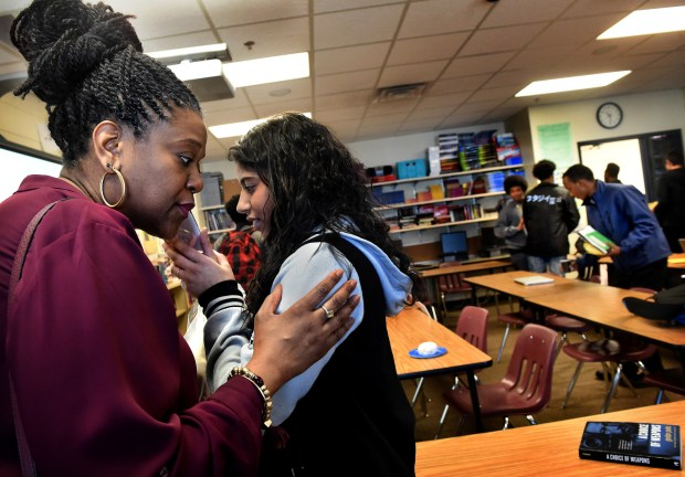 """At the end of a class, Robin Hickman, left, grandniece of Gordon Parks, listens on a cell phone to a recording of Tanisha Santiago's """"Poetry Outloud"""" competition at Gordon Parks High School in St. Paul on Wednesday, March 8, 2017. Every student in the school rotates through a three-week class, researching, writing and reading excerpts from Parks' autobiography, 'A Choice of Weapons,' which is on the desk to the right. Jean Pieri / Pioneer Press"""