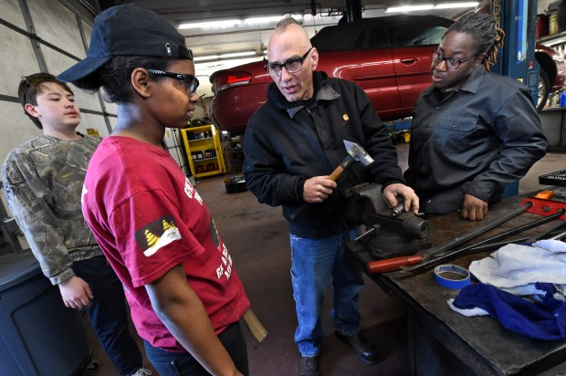 Matt Lijewski, center, teaches how to get a stuck lug nut out of a socket to students, from left: Kai Wackerfus, Millenium Amha and Angelica Tonge, at St. Paul Public Schools Central High School Service Station in St. Paul on Wednesday, March 22, 2017. Lijewski, who runs the shop, had tools stolen from his vehicle along with the tools stolen from various locations in the shop. (Jean Pieri / Pioneer Press)
