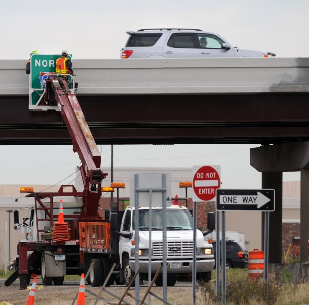 FILE -- Road construction is wrapping up at the Highway 5/Interstate694 interchange in Oakdale. A worker hangs a sign Wednesday morning, October 20, 2010. (Pioneer Press: Chris Polydoroff)
