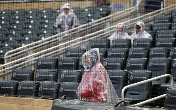 An usher and some rain-protected fans wait for a baseball game between the Minnesota Twins and the Chicago White Sox on Friday, April 14, 2017, in Minneapolis. (AP Photo/Jim Mone)
