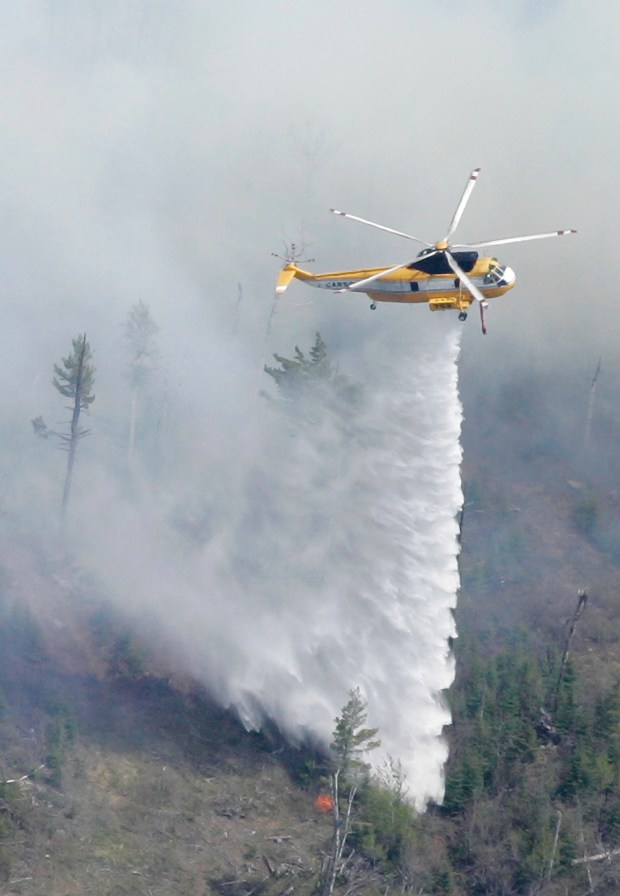 In this May 13, 2017, file photo, a firefighting helicopter drops water on flames along the Gunflint Trail near Loon Lake northwest of Grand Marais, Minn., as firefighters in the air and on the ground battle the week old fire that has destroyed nearly 83 square miles in Minnesota and Canada. The fire began May 5, 2007, with a seemingly innocent campfire. It quickly blew out of control, fanned by erratic winds and fueled by tinder dry conditions. It took 1,000 firefighters from around the country a week to finally corral it. (AP Photo/Jim Mone, File)