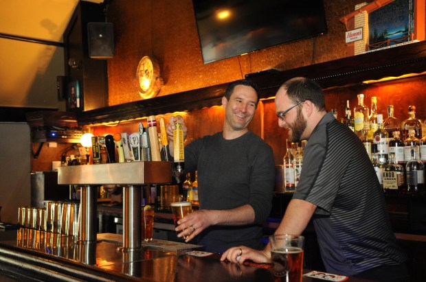 Thomas LaFleche, left, owner of Brunson's Pub, pours a beer for a customer while chatting with bartender Chris Fabel at the new pub at 956 Payne Ave. on the East Side of St. Paul. (Ginger Pinson / Pioneer Press)