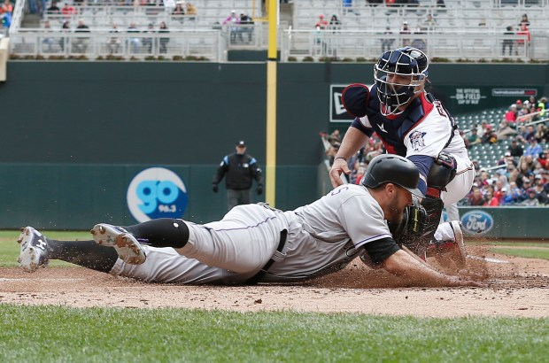 Colorado Rockies' Mark Reynolds, left, is tagged out at the plate by Minnesota Twins catcher Chris Gimenez as he tried to score on an RBI single by Ian Desmond in the third inning during the first baseball game of a doubleheader, Thursday, May 18, 2017, in Minneapolis. (AP Photo/Jim Mone)