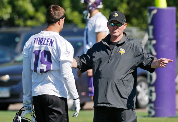 Minnesota Vikings head coach Mike Zimmer, right, talks with wide receiver Adam Thielen during an NFL football team practice Tuesday, June 6, 2017, in Eden Prairie, Minn. Zimmer is back at Vikings practice after being told to take a leave while recovering from an eighth eye surgery. (AP Photo/Jim Mone)