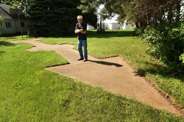 Jim Jansen of Cottage Grove poses with a concrete arrow next to his house, built as a part of a ground-based navigation system extending from New York to California in the 1920's and 30's, Monday, June 26, 2017. The arrow was painted bright-yellow and was next to a 50-foot tower with a beacon atop it. United States Postal Service pilots delivering mail would look for the beacon and then follow the arrow to Holman Field in St. Paul. (Scott Takushi / Pioneer Press)