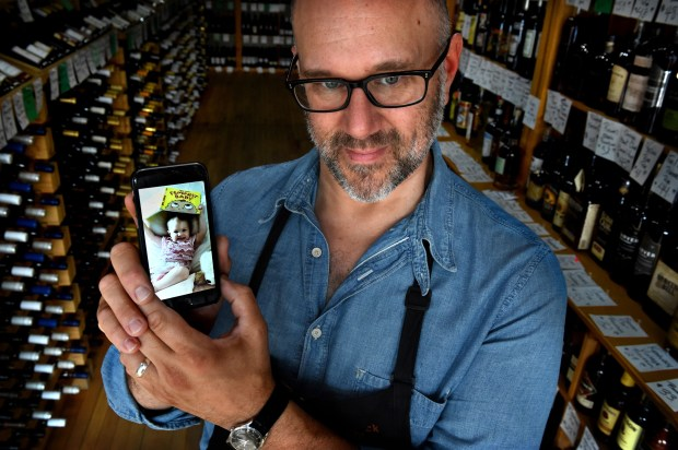 """""""I was raised that Sunday is family day. I have a 16-month-old daughter, Evelyn, that I'd rather spend time with,"""" said Chuck Kanski, co-owner of Solo Vino in St. Paul, as he shows a photo of his girl Wednesday, June 28, 2017. Solo Vino is one of the handful of stores who are planning not to open this Sunday after the change in state law. (Jean Pieri / Pioneer Press)"""