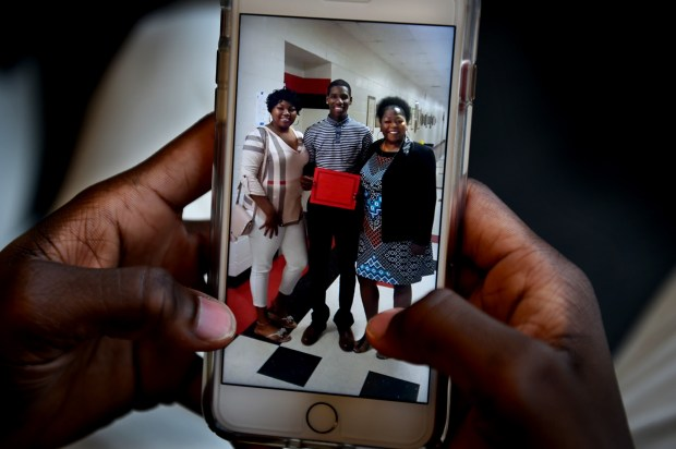 Marques Watson, 18, talks about being the first recipient of an annual $5,000 Philando Castile memorial scholarship for St. Paul Central High School graduates, Friday, June 23, 2017. He shows a cell phone photo holding his award while standing between Philando Castile's sister, Allysza Castile, and Castile's mom, Valerie Castile. (Jean Pieri / Pioneer Press)