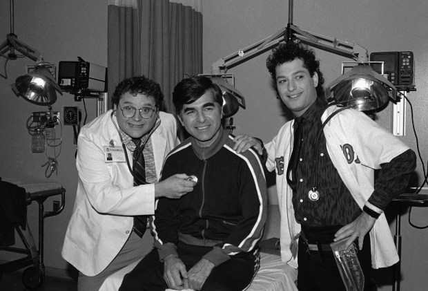 "FILE - In this Nov. 9, 1984, file photo, Massachusetts Gov. Michael Dukakis, center, receives treatment from Stephen Furst, left, and Howie Mandel, stars of NBC's television series ""St. Elsewhere,"" in Los Angeles during taping for an episode in which Dukakis played himself and received treatment for a foot injury suffered while jogging. Furst's family says the ""Animal House"" actor has died. Nathan Furst said Saturday, June 17, 2017, that his father died of complications from diabetes. Stephen Furst was 63. He died Friday at his home in Moorpark, Calif., north of Los Angeles. (AP Photo/Robert Gabriel, File)"