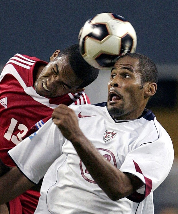 Cuba's Maykel Galindo (13) and United States' Tony Sanneh both try to head the ball in the second half, Thursday, July 7, 2005, in a CONCACAF Gold Cup game in Seattle. The U.S. won, 4-1. (AP Photo/Elaine Thompson)