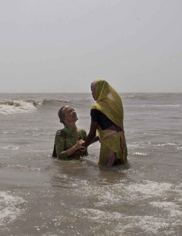 An Indian woman helps Elizabeth Brenner, left, a mother from Minnesota, take a dip in the waters of Gangasagar in West Bengal, India, on April 13, 2017.. Brenner was on a pilgrimage following the last footsteps of her son, who died while studying abroad in India. She believes that part of her son's remains flowed across India through the Ganges river into the Bay of Bengal. (Rishabh R. Jain / Associated Press)