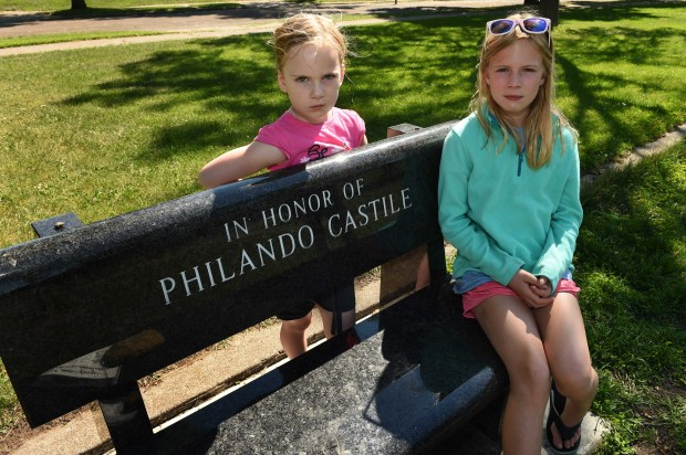 """Sisters Audrey, 5, and Natalie Drake, 9, right, sit by the Philando Castile memorial bench at J.J. Hill Montessori School in St. Paul, where they attend school and knew """"Mr Phil"""" Monday, July 3, 2017. (Scott Takushi / Pioneer Press)"""
