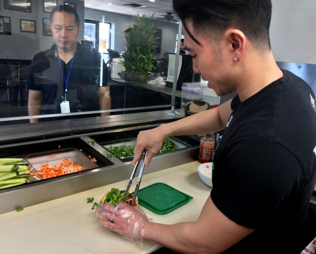 iPho co-owner Thinh Pham fills a banh mi order at the St. Paul restaurant's sandwich counter on July 12, 2017. (Nancy Ngo / Pioneer Press)