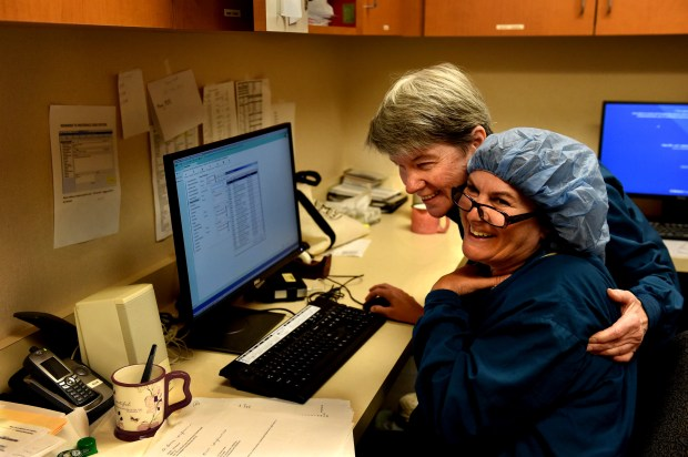 After Alyce Brekke, left, puts Knitted Knockers in plastic containers in an office cupboard, she gives a little hug to her colleague, Virginia Amberg, a surgical tech who also knits the breast prostheses at Lakeview Hospital, in Stillwater Thursday, June 29, 2017. Brekke and friends have made more than 100. The colorful and light cotton breasts - stuffed with microfiber filing - are a user-friendly alternative to silicone breast prostheses which can be hot, heavy and sticky. She recently received a $1,000 grant from Lakeview Hospital Foundation to purchase yarn for the project. (Jean Pieri / Pioneer Press)
