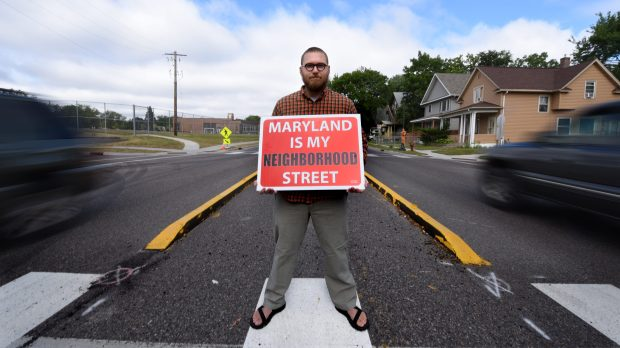 "Eric Saathoff, a resident of St. Paul's Payne-Phalen neighborhood, stands in a ""pedestrian refuge"" on Maryland Avenue at Greenbrier Street Thursday, July 13, 2017, with a sign he developed to support experimental driving restrictions underway since June. (Dave Orrick / Pioneer Press)"