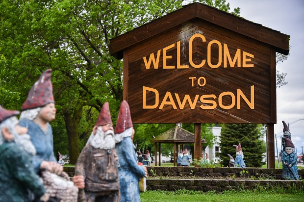 """Wooden gnome statues surround the """"Welcome to Dawson"""" sign in Dawson, Minn., which has proclaimed itself Gnometown. Every year, a statue is awarded to a Dawson resident and created in that person's image. (Salwan Georges, Washington Post)"""