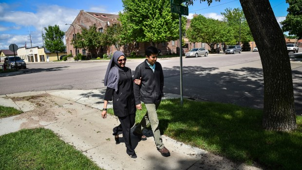 Dr. Ayaz Virji, 42, and his wife Musarrat Virji, 36, walks home from work on a May day in Dawson, Minn. (Salwan Georges, Washington Post)