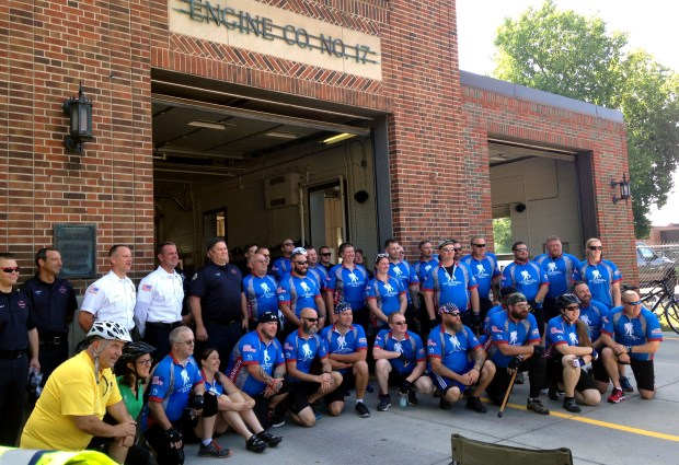 People participating in a Wounded Warrior bicycle ride pose for a photo during a break at St. Paul Fire Station No. 17 on Payne Avenue, near Maryland Avenue, on the morning of Friday, July 28, 2017. (Mara H. Gottfried / Pioneer Press)