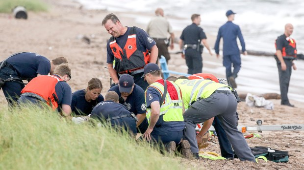 Personnel from the Duluth Fire Department and Gold Cross Ambulance work Thursday evening, Aug. 10, 2017, administering CPR to a girl who was pulled from Lake Superior at the Park Point Beach in Duluth, Minn., as other emergency personnel continue to search for another missing swimmer. The girl's father was also pulled from the lake about 50 minutes later. Both died. (Clint Austin / Forum News Service)
