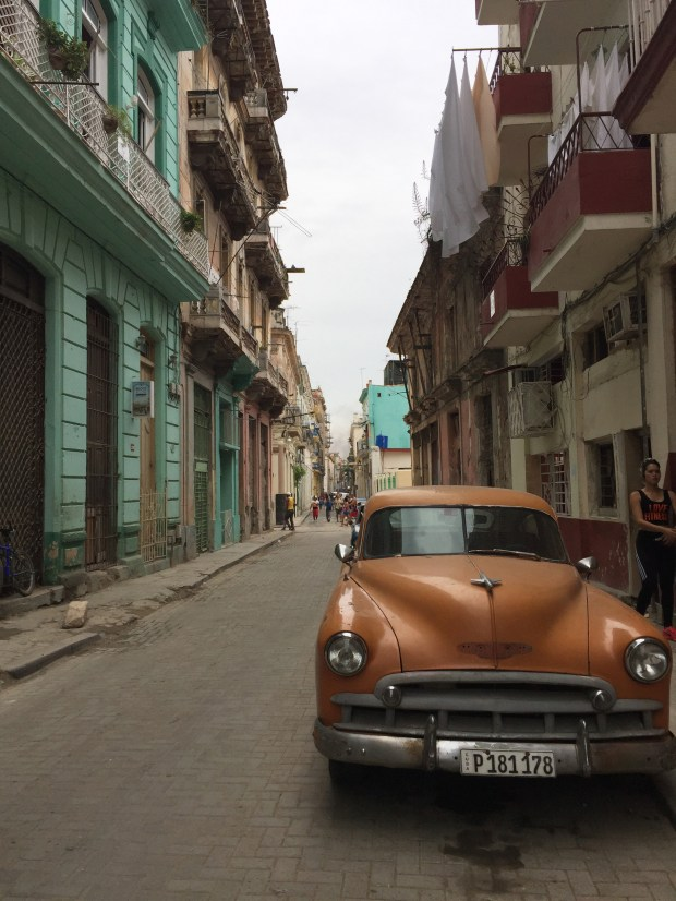 A beat-up orange car is parked on a narrow street in old Havana in April 2017. (Courtesy of Jackie Gaston)