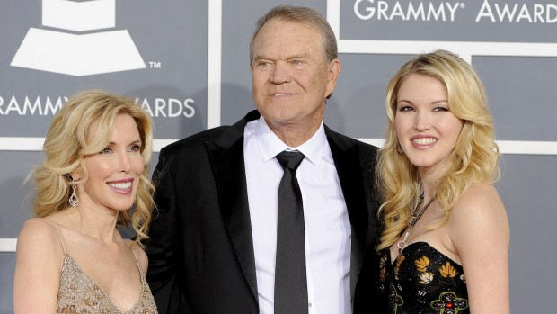 """In this Feb. 12, 2012 file photo, Glen Campbell, center, Kim Woolen, left, and Ashley Campbell arrive at the 54th annual Grammy Awards in Los Angeles. Campbell, the grinning, high-pitched entertainer who had such hits as """"Rhinestone Cowboy"""" and spanned country, pop, television and movies, died Tuesday, Aug. 8, 2017. He was 81. Campbell announced in June 2011 that he had been diagnosed with Alzheimer's disease. (AP Photo/Chris Pizzello, File)"""