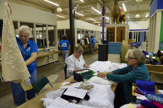 From left: Sue Arnett, Susi McCune and Faith Clover organize and judge the Table Linens category in the Creative Activities Building at the Minnesota State Fair on Aug. 15, 2017. (Scott Takushi / Pioneer Press)