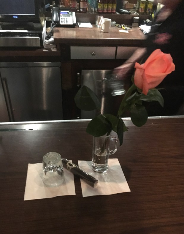 """Employees and family members marked the spot where Earl """"Red"""" Schoenheider always sat at Red's Savoy Pizza in St. Paul with an upside down shot glass, a rose in his beer glass and a cigar. Red, 82, who bought the restaurant in 1965, died Monday, Aug. 21, 2017. (Courtesy of the Schoenheider family)"""