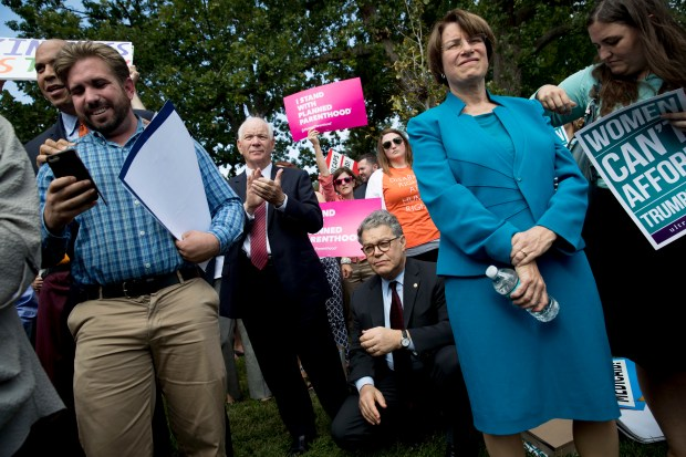 From left, Sen. Cory Booker, D-N.J., Sen. Ben Cardin, D-Md., Sen. Al Franken, D-Minn., and Sen. Amy Klobuchar, D-Minn., stand with health care advocates, grassroots activists, and concerned constituents at a rally outside the Capitol in Washington, Tuesday, Sept. 19, 2017. Senate Republicans begin another push to repeal the Affordable Care Act with the Graham-Cassidy proposal. (AP Photo/Andrew Harnik)