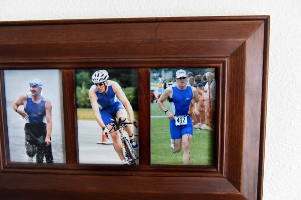 On his living room wall, Mark Kedrowski has photos of himself in a triathalon. (Jean Pieri / Pioneer Press)