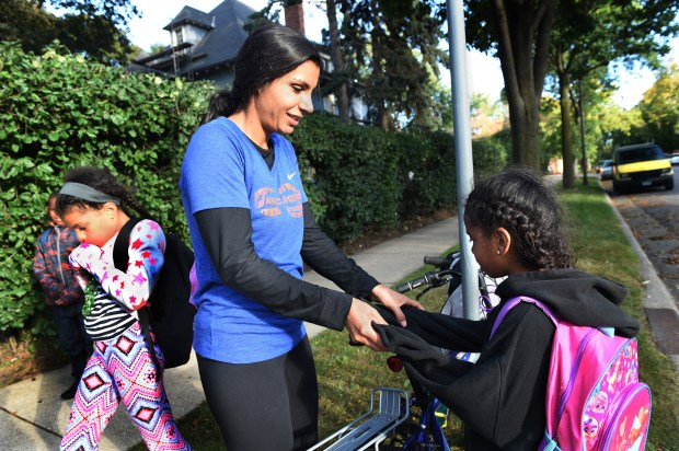 Nour Tamimi, center, tries to warm her daughter Yasmin's cold hands as she waits for a school bus with her sister, Doniah, left, in St. Paul Wednesday, Sept. 27, 2017. Tamimi, a refugee, will be running the Twin Cities Marathon for the first time this year. She is a participant in Mile in My Shoes, a program that helps homeless and disadvantaged people take up running.  (Jean Pieri / Pioneer Press)