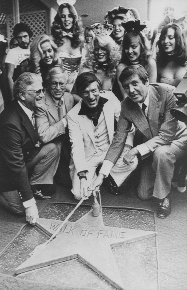 "In this April 10, 1980, file photo, Chairman of the Board, Playboy Enterprises Inc., Hugh Hefner, center, receives a star on the Hollywood Walk of Fame in Los Angeles. Honorary Mayor of Hollywood, Monty Hall, right, holds the rope attached to the new star with Hefner. Former ""Let's Make a Deal"" host Hall has died after a long illness at age 96. His daughter Sharon Hall says he died Saturday, Sept. 30, 2017, at his home in Beverly Hills, Calif. (AP Photo/ File)"
