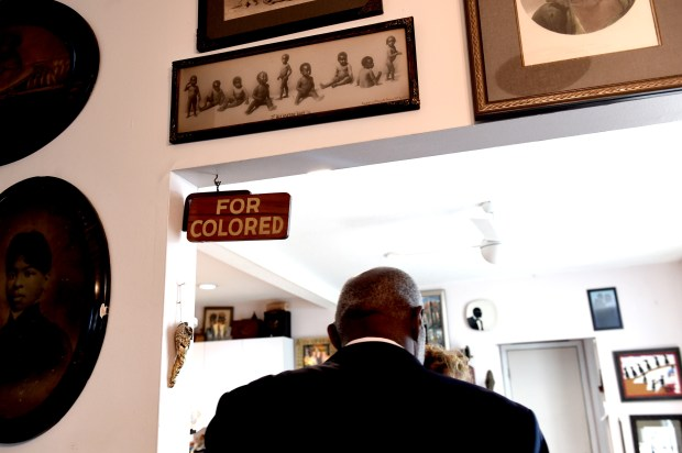 "Alan and Diane Page walk into their kitchen under a ""For Colored"" sign and a framed 1897 collection of photographs of African-American babies labeled ""Alligator Bait."" (Jean Pieri / Pioneer Press)"