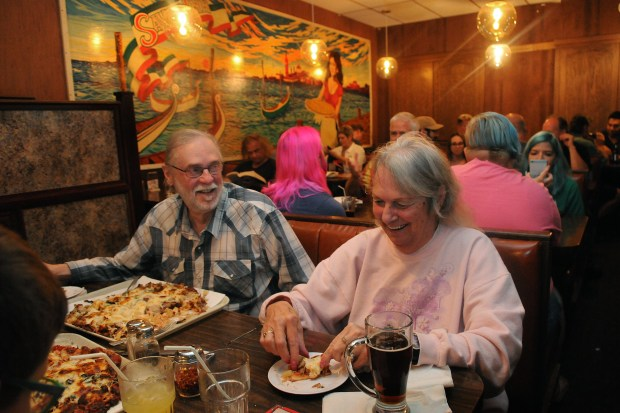 """""""I eat pizza crazy. I eat the top off first and then I eat the crust,"""" said Clare Hix,right, who was a waitress for 26 years at Red's Savoy Pizza in St. Paul prior to retiring two years ago at the age of 76. """"This is the only place I would order pizza,"""" Hix said. Sitting to her left is her brother, Richard Hix. Long lines of regulars to Red Savoy Pizza showed up early on Saturday, September 16, 2017, the last day the Pizza spot on East 7th Street would be open. The owners are closing this location after founder, Earl """"Red"""" Schoenheider, who has owned the restaurant since 1965 died in August. The building, which the family does not own, needs six figure renovations. (Ginger Pinson / Pioneer Press)"""