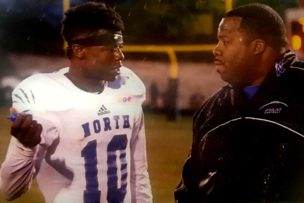 Former Minneapolis North quarterback Tyler Johnson, now a Gophers receiver, discusses kicking a field goal with Polaris coach Charles Adams in their game against St. Paul Central in 2015. (Courtesy of Charles Adams)