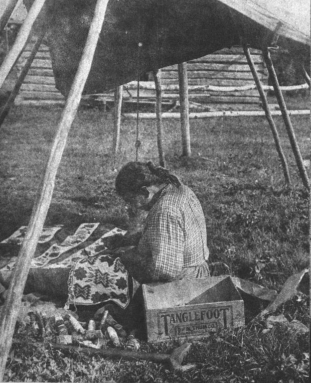 A Red Lake bead artist in this photo, dating to the late 1880s or early 1890s, exemplifies the simple resources used by Ojibwe women in creation of these stunning bags and the evolving Ojibwe gashkibidaagan styles in Minnesota. In the foreground, by her crutch, are her beads, strung on long threads wound around rolled pieces of birth bark or paper. She works on both a loom-woven bag and a spot-stitch applique bag. The spot-stitch applique beaded bag parts with floral motifs are laid out off to her right, and on her lap is a loomed pocket panel with geometric motifs that she is attaching to a foundation cloth. (Courtesy of Minnesota Historical Society Press)