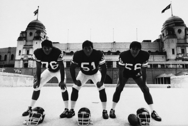 Members of the Minnesota Vikings are shown during a training session at Wembley Stadium in London, Aug. 5, 1983. They are, from left to right: Tim Irwin (76), tackle, who weighs in at 275 pounds, Jim Hough (51), guard, who weighs 267 pounds and David Huffman (58), center, weighing 255 pounds. Their team meets the St. Louis Cardinals at the Wembley Stadium in a pre-season match Saturday. (AP Photo/Bob Dear)