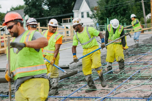 In this Aug. 28, 2017, photo, two Thor Construction employees joke with each other as they smooth cement on the site of the company's new headquarters in north Minneapolis. (Evan Frost/Minnesota Public Radio via AP)
