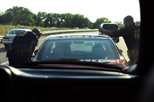 St. Paul police officers Isaac Palmer, left, and Ryan Anderson, of the gang and gun unit, make a traffic stop on Interstate 94 in St. Paul on July 11, 2017. Police had recently found a passenger in the car with a gun and he was charged with possession of a pistol without a permit. (Scott Takushi / Pioneer Press)