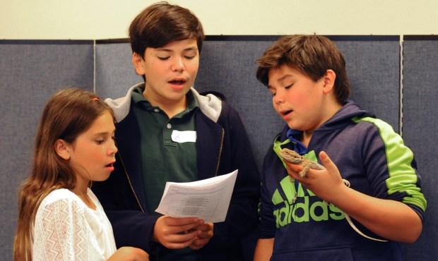 """Maria Odegard, 9 sings """"All Creatures Worship God Most High"""" with her brothers, Evan, 13, and Marcos, 9, who is holding Kiwi, a one-year-old, Bearded Dragon during the Blessing of the Animals annual religious ceremony conducted by Associate pastors,  Javen Swanson and Lois Pallmeyer at Gloria Dei Lutheran Church on Snelling Ave. in Highland Park on Sunday, October 1, 2017.  (Ginger Pinson / Pioneer Press)"""