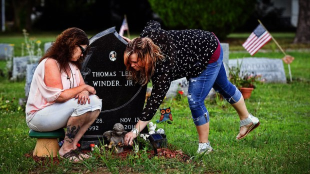 Tina Snyder, left, and Courtney Winder visit the grave of - respectively - their son and brother in July. The 24-year-old died of an opioid overdose in November. Winder lost another brother to an overdose in 2014. Must credit: Washington Post photo by Michael S. Williamson