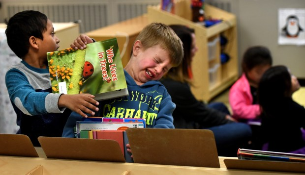Manna Asif, left, accidentally bumps into Gabe Skaar as they get books in Julie Heroff's preschool class at Castle Elementary School in Oakdale on Wednesday, Oct. 11, 2017. (Jean Pieri / Pioneer Press)