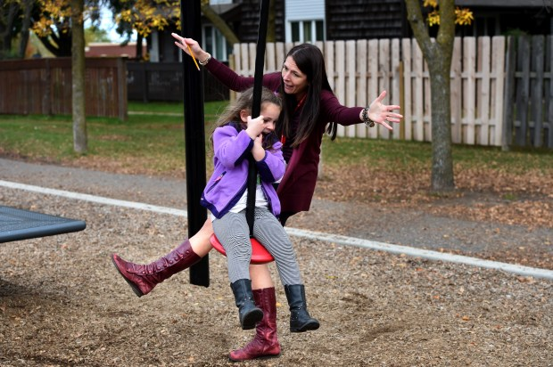 Principal Bridget Bruner dances out of the way after pushing preschooler Lydia Pettey on the zipline during recess at Castle Elementary School in Oakdale on Wednesday, Oct. 11, 2017. (Jean Pieri / Pioneer Press)