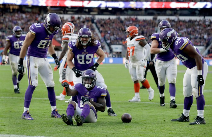 Minnesota Vikings running back Jerick McKinnon (21), center, sits on the turf as he celebrates after scoring a touchdown during the second half of an NFL football game against Cleveland Browns at Twickenham Stadium in London, Sunday Oct. 29, 2017. (AP Photo/Matt Dunham)