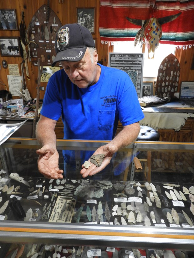 Gary Henschel, owner of Henschel's Indian Museum, shows visitors some of the archeological artifacts found on his property. (William M. Gurstelle)