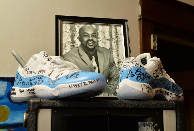 A photo of Brandon Roberts, who was fatally shot outside a bar on St. Paul's University Avenue, and a pair of shoes signed by family and friends are seen in the St. Paul home of his aunt on Nov. 1, 2017.  The case remains unsolved.  (Pioneer Press / Scott Takushi)