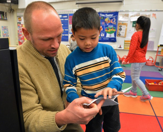 Hae Nay Taw reads a booklet he has written about animals to teacher Matt Shimon at Bruce Vento Elementary School in St. Paul, where kindergarteners in Shimon's class have gone back to student choice and learning through play, after a focus on formal, teacher-led instruction led to behavioral problems, Nov. 21, 2017. (Scott Takushi / Pioneer Press)
