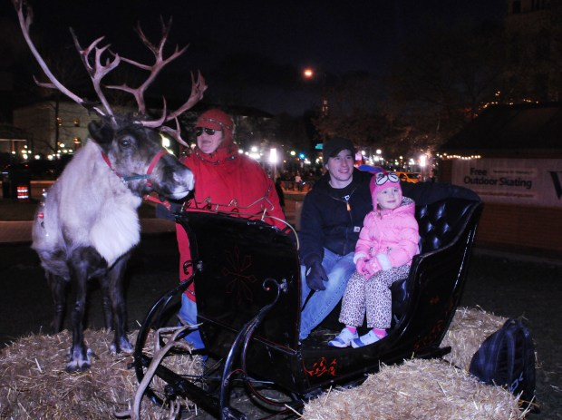 """Sam and Sophia Albert of Plymouth have their photo taken in a sleigh set with Yukon, an 11-year-old reindeer and his handler, Jane Teubert who called herself, """"the elf"""" up by the WinterSkate ice rink during opening festivities of WinterSkate and the holiday tree lighting ceremony at Rice Park on Saturday, November18, 2017. (Ginger Pinson / Pioneer Press)"""