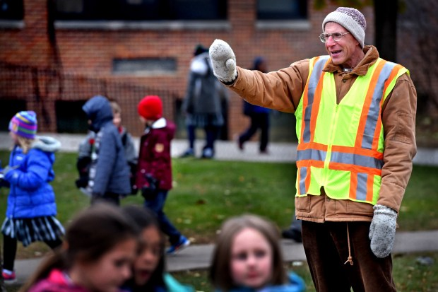 Crossing guard Chuck Nehls waves to children crossing the street on the way to recess at Highland Catholic School in St. Paul, Wednesday, Nov. 15, 2017. Last month community members donated over $2,500 to get him a new kitten and medications or procedures the cat would need, after his cat, who was his best friend, died. (Jean Pieri / Pioneer Press)