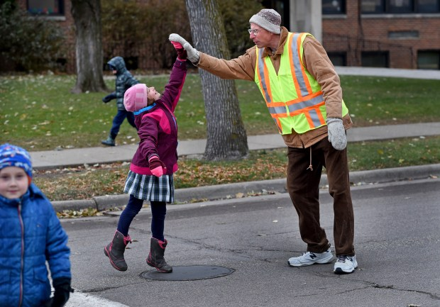 Crossing guard Chuck Nehls greets a girl as she crosses the street to go to recess at Highland Catholic School in St. Paul, Wednesday, Nov. 15, 2017. Last month community members donated over $2,500 to get him a new kitten and medications or procedures the cat would need, after his cat, who was his best friend, died. (Jean Pieri / Pioneer Press)